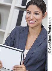Beautiful young Latina Hispanic woman or businesswoman in smart business suit sitting at a desk in an office using a tablet computer