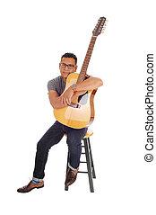 hispanic, mal, sittande, med, hans, guitar.