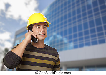 Hispanic Male Contractor on Phone in Front of Building