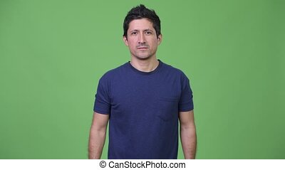 Hispanic man against green background - Studio shot of...