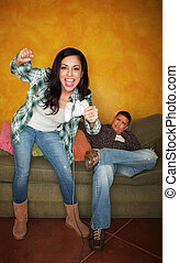 Hispanic man bored while wife plays video game