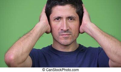 Hispanic man covering ears as three wise monkeys concept -...