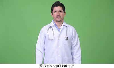 Hispanic man doctor against green background
