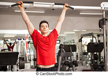 Hispanic man doing some pullups at a gym