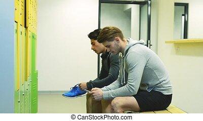 Hispanic man in gym resting, holding smart phone, listening musi