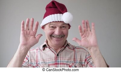 Hispanic man in red christmas hat smiling and waving with his hand.