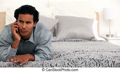 Hispanic man on the phone lying on his bed