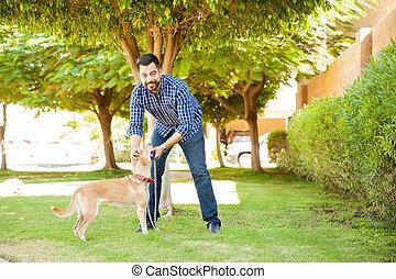 Hispanic man playing with his dog