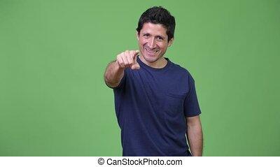 Hispanic man pointing to camera - Studio shot of Hispanic...