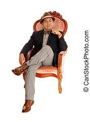 Hispanic man relaxing in a armchair.