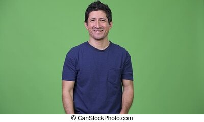 Hispanic man smiling with arms crossed - Studio shot of...