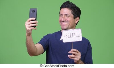 Hispanic man taking selfie with paper sign - Studio shot of...
