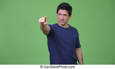 Hispanic man thinking while pointing finger - Studio shot of...