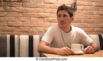 Hispanic man thinking while relaxing at the coffee shop -...