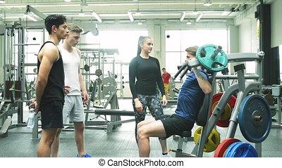 Hispanic man training in gym, doing machine shoulder press.