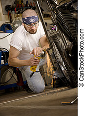 Hispanic man using grinder tool on the front fork of motorcycle