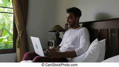 Hispanic Man Using Laptop Computer Sitting On Bed Guy Type...