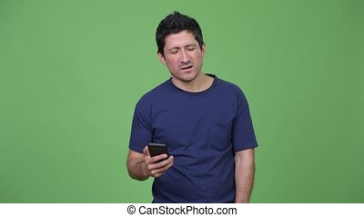 Hispanic man using phone and getting bad news - Studio shot...