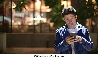 Hispanic man using phone while exploring the city streets at night