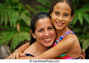 Hispanic mother and daughter hugging