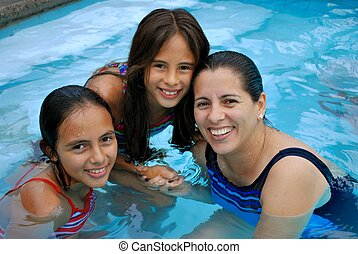 Hispanic mother and daughters in a pool