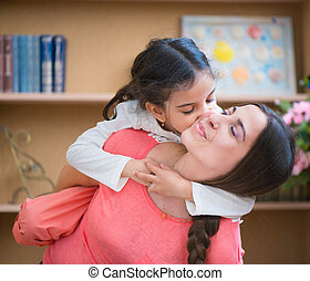 Hispanic mother and little daughter playing at home