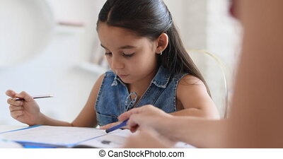 Hispanic Mother Helping Girl Doing School Homework At Home