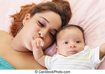Hispanic mother kissing her baby hand.  Focus on the mother.