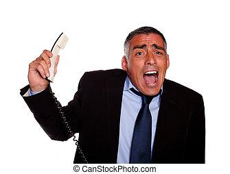 Hispanic senior businessman screaming with a phone