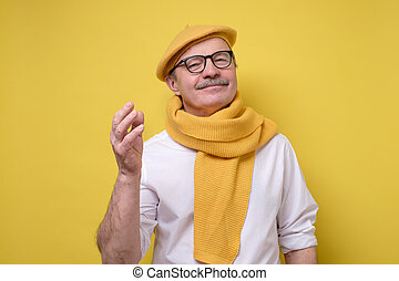 Hispanic senior man in yellow beret and scarf looking with a...