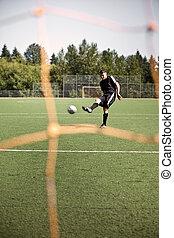 Hispanic soccer or football player kicking a ball