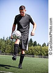 Hispanic soccer or football player kicking a ball - A shot...