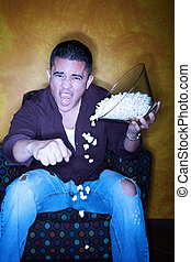Hispanic sports fan with popcorn watching television