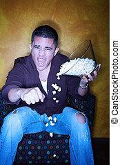 Hispanic sports fan with popcorn watching television