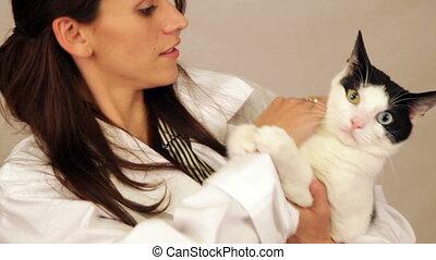 Hispanic Veterinarian Holding Cat in Arms