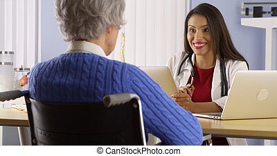 Hispanic woman doctor talking with elderly patient