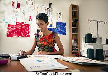 hispanic woman doing budget in fashion designer atelier -...