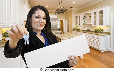 Hispanic Woman In Kitchen Holding House Keys and Blank Sign