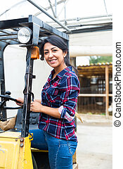 Hispanic woman sits down to work behind the wheel of a forklift truck in an enterprise.