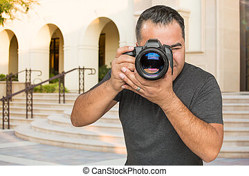 Hispanic Young Male Photographer With DSLR Camera Outdoors