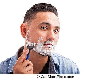 Hispanic young man shaving his beard
