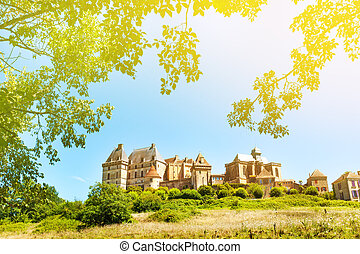 Historic Biron castle in France under blue sky