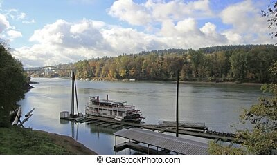 Historic Sternwheeler Docked Along Willamette River in Oregon City in Fall Season with Moving White Clouds Blue Sky and Water Reflection Time Lapse 1920x1080