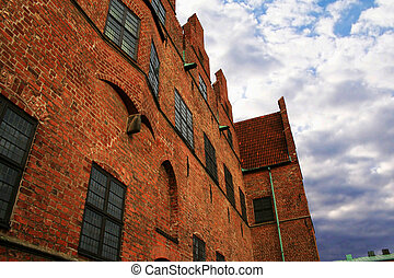 historic brick building with cloudy sky