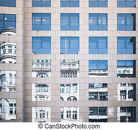 historic building mirrored in glass facade of modern office building