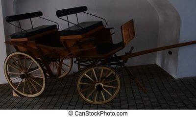 Historic coach at dark courtyard entry. - Historic coach at...