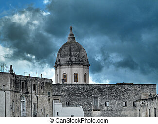 Historic dome standing out in the cloudy sky. Monopoli. Apulia.
