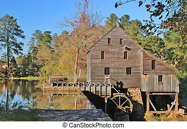 Historical Yates Mill, a restored gristmill in Raleigh, North Carolina surrounded by Autum colors