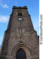 Historic landmark evangelist church clock tower front gates and blue sky in United Kingdom