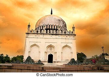 Historic Quli Qutb Shahi Tombs against bright orange sky